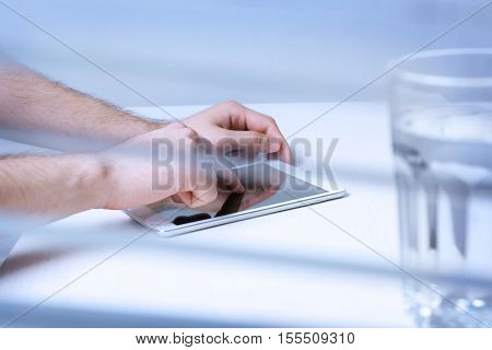 Man holding tablet in hands. View through blinds