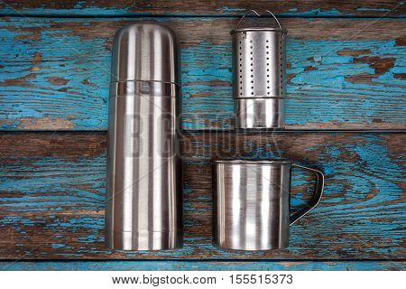 Metal thermos and mugs on a wooden background. Kitchenware. Tea accessories.