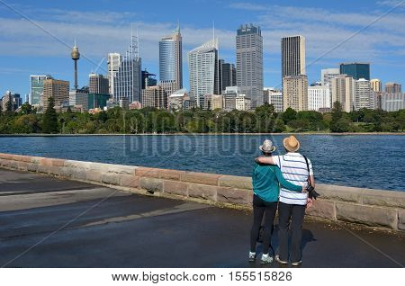 Senior Couple looks at Sydney Central Business District skyline as view from the Royal Botanic Gardens in Sydney New South Wales Australia
