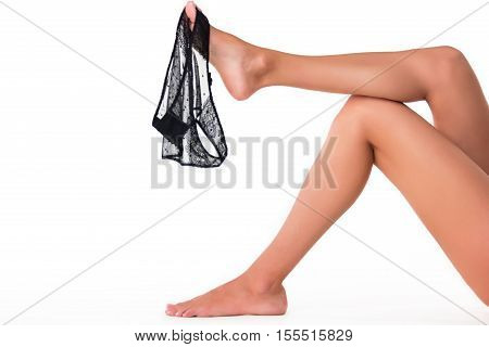 Panties hanging on foot. Female legs on blank background. Tease and seduce. Men can't resist.