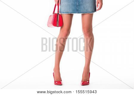 Legs wearing heels and handbag. Short jeans skirt. Emphasize your femininity. Look stylish this summer.