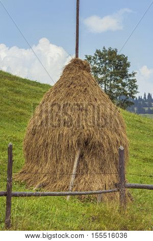Haystack Mountain. Traditional mountain haystack in Romania. Haystack in rural area in Romania. Romanian rural landscape with traditional haycock.