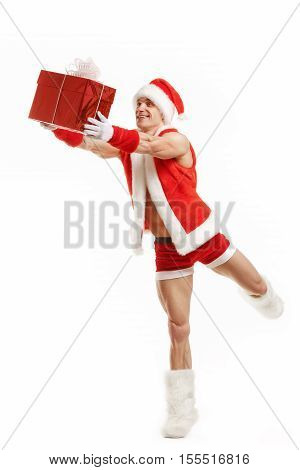 Bodybuilder Santa Claus gives a gift in red box. Cheerful fitness Santa Claus holding a red box. Muscular Santa Claus isolated over white background. Santa Claus isolated