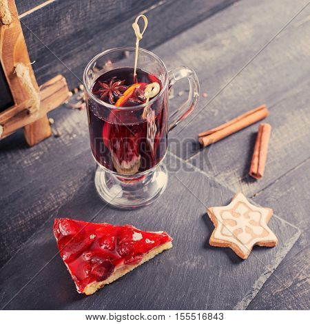 Mulled wine with strawberry pie and Christmas cookies on the wooden background