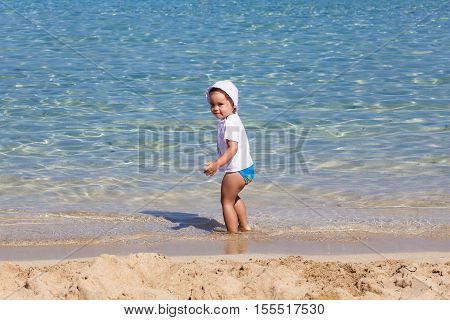 Little child girl is playing on sandy beach near blue sea