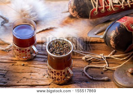 Leaf tea brewed in the strainer on old wooden table