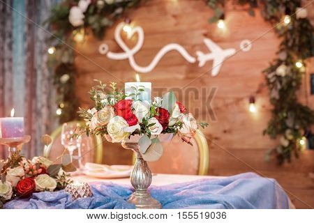 candle holder with a candle and a bouquet of roses for the wedding table