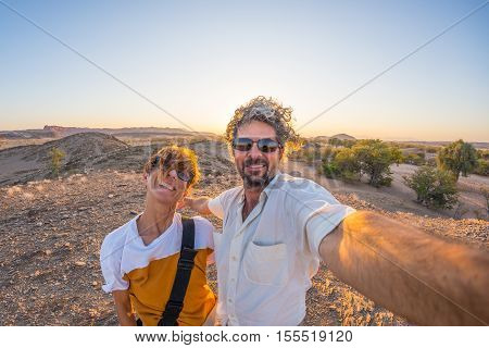 Smiling adult couple taking selfie in the Namib desert Namib Naukluft National Park main travel destination in Namibia Africa. Fisheye view in backlight adventures in Africa.
