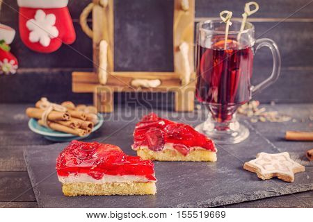 Mulled wine and strawberry pie on the wooden background. Christmas decoration. Vintage design.