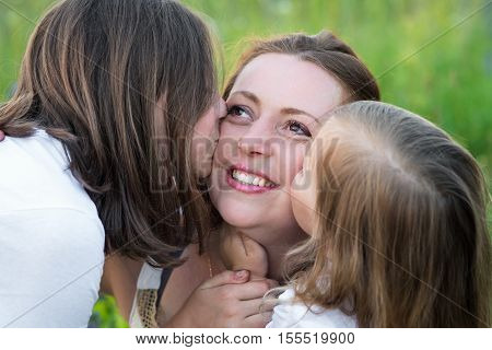 two daughters, Kiss mom in her cheeks