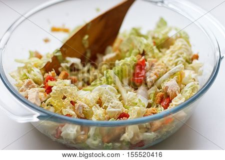 salad of cabbage crackers tomato chicken in a glass pot