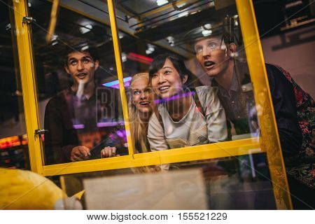 Cheerful young friends playing toy grabbing game at amusement park. Happy woman selecting a random soft toy in a vending machine.