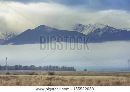The Romanian Southern Carpathian Mountains In The Morning Light With Fog Overground And The Snowy Pe