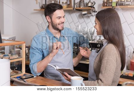 Exiting conversation. Cheerful young waiters smiling and having conversation while standing at the counter