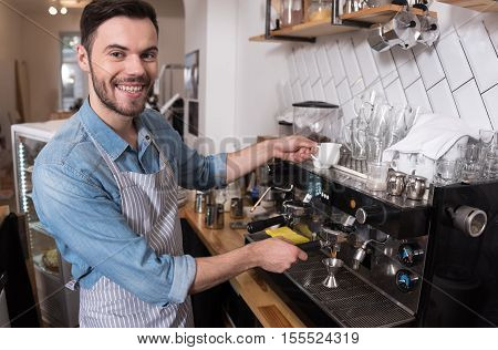 Inspired barista. Pleasant handsome man smiling and using coffee machine while standing behind the bar.