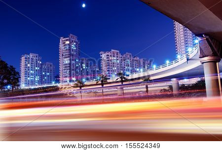 Modern city buildings and viaducts at night.