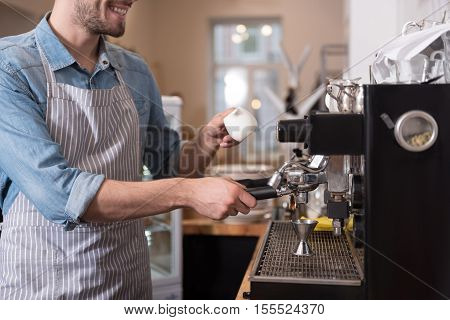 Coffee is my passion. Close up of emotional barista smiling and making coffee by coffee machine while standing at the bar.