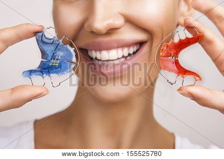 Dental and Ortho - Beautiful Smiling Girl Holding Retainer for Teeth (Braces for Teeth). Stomatology Orthodontics Dental Theme Methods of Teeth (Bite) Correction and fix. White Smile Close-up.