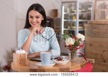 Delightful coffee break. Attractive satisfied delighted woman smiling and relaxing while visiting a coffee shop.
