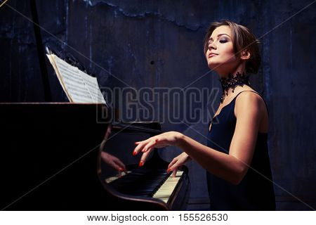 Mid side shot of elegant woman starts piano performance while sitting isolated in studio. She is using sheet music while sitting tall and proud at the piano with shoulders down