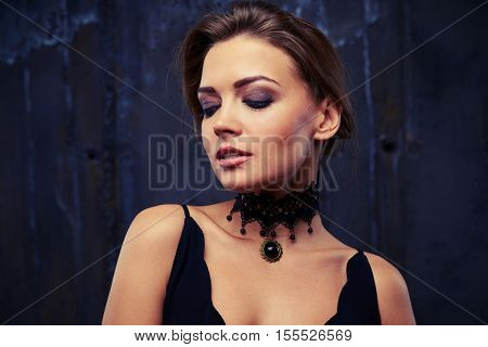 Beautiful young woman with smoky makeup looking down, wearing jewelry as a compositional element to the eveningwear, close-up shot