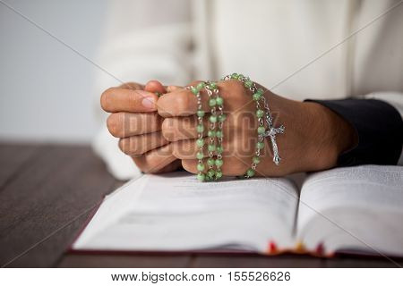 Praying hands of woman with a rosary and bible on wooden desk