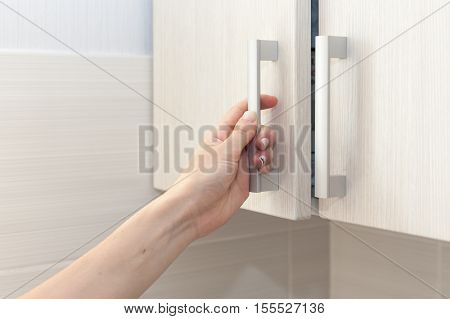 Female hand open the cupboard doors close up