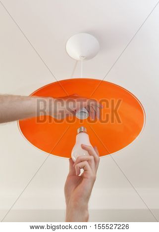 Close-up of energy-saving LED light bulb in the human hand the replacement of the lamp in the ceiling luminaire made of orange ground glass.