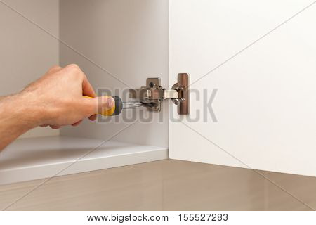 A workman fixing cabinet with screwdriver in kitchen