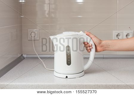 Electric Kettle in hand on the background of the kitchen.