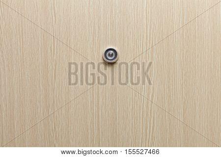 Lens peephole on new wooden door closeup