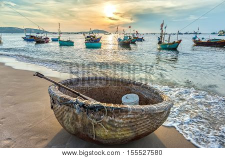 Phan Thiet, Vietnam - July 26th, 2016: Basket boat before dawn as the sun slowly rise to express the rest of the season when fishermen fish on, languish waiting to be put to sea