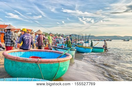 Phan Thiet, Vietnam - July 26th, 2016: Landscape brisk trade in fish at Mui Ne fishing village on a sunny morning, which attracts tourists to visit
