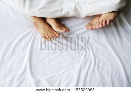 Feet of couple in comfortable bed. Close up of feet in a bed under white blanket. Bare feet of a man and a woman peeking out from under the cover.Top view with copy space (selective focus)