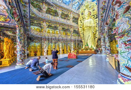 Lam Dong, Vietnam - August 1st, 2016: Pilgrims praying peacefully in the temple. This is great architectural works made from pieces of crockery specially assembled only in Lam Dong, Vietnam