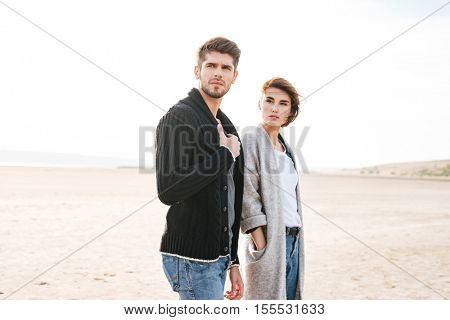 Portrait of a beautiful young casual couple standing at the beach and looking away