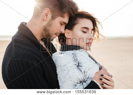 Close up portrait of a beautiful tender couple in love hugging on the beach
