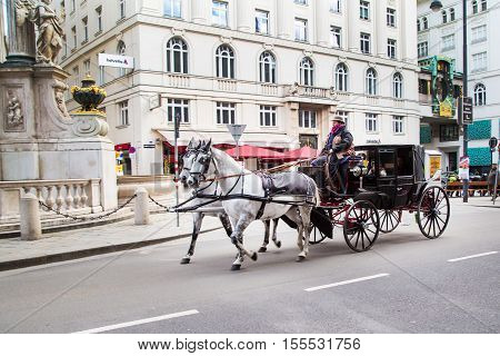 Vienna, Austria - April 3, 2015: City center street view, people walking, Vienna clock and fiaker with white horses  in Vienna, Austria