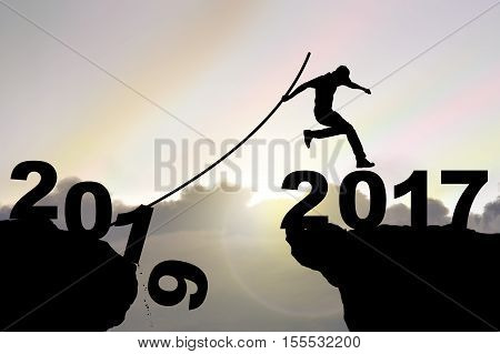Man jumping over precipice with pole vault on Iridescence sky background business people success happy new year 2017 concept