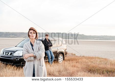 Beautiful young woman standing outdise with man leaning on car on the background