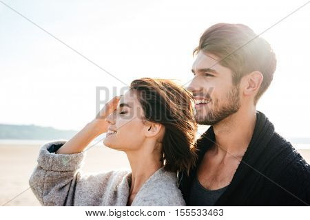Portrait of an attractive young couple having good time together at the beach in autumn