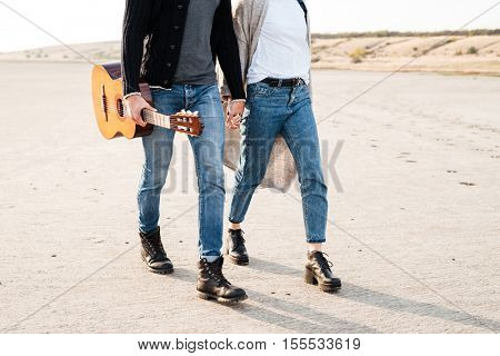 Cropped image of a casual couple walking at the beach with guitar