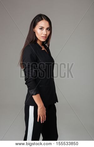Pretty brunette business woman standing in black suit over gray background