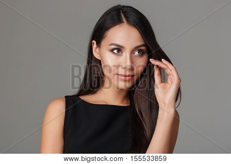 Close up portrait of a beautiful young woman with make up and long hair isolated on a gray background