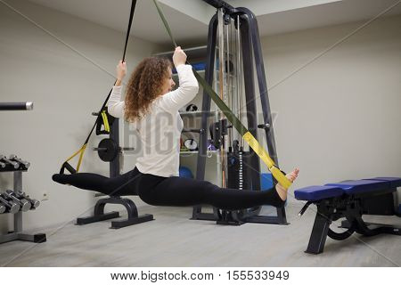 Woman does exercises of Fly Stretching in gym with fitness equipment
