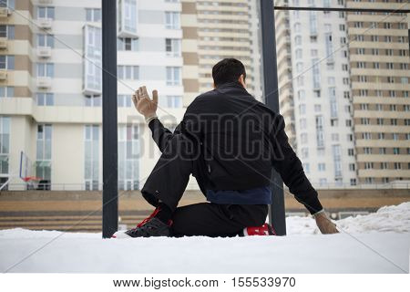 Man does yoga exercises on sport playground in yard at winter, back view