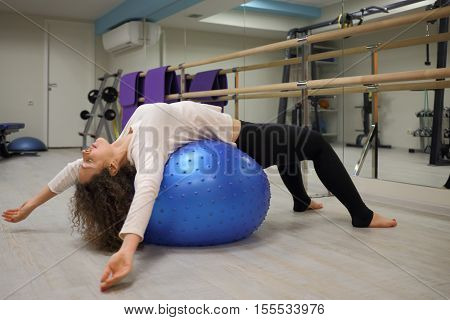 Woman does exercises on fitball in gym with fitness equipment and mirror