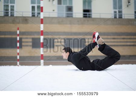 Man in black does exercises on playground near building at winter day