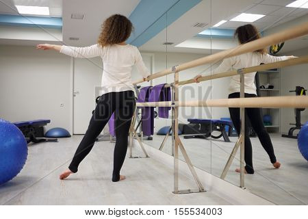 Woman does stretching exercises near ballet bar in gym with fitness equipment, back view