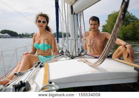 Woman in sunglasses and man sit on yacht during sailing at summer